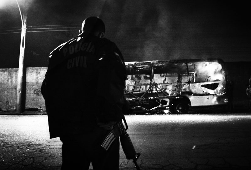 A policeman stands in front of a bus set fire by an arsonist. Bus arson often happens in Rio, as violence and street crimes are very rampant. May 2007.
