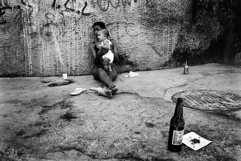 In a favela of Cidade Nova, woman and her baby refuge into a sidewalk from humid and hot weather. Feb 2008.