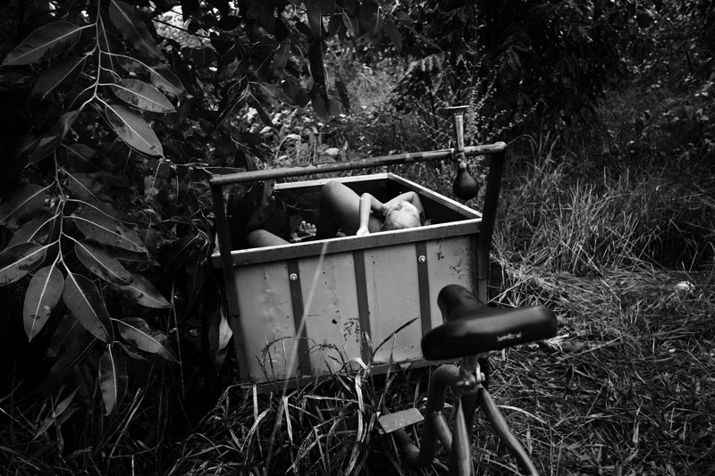Bodies of a mother and two kids remain in a bike cart, in a forest of Baixada Fluminense, after they were killed and dumped by their own family member. Although the motivation is unknown, this type of fatal domestic violence is a kind of common in Rio, as violence and street crime are tremendously rampant in the community and as those factors affect its people in a variety of dimensions. June 2007.
