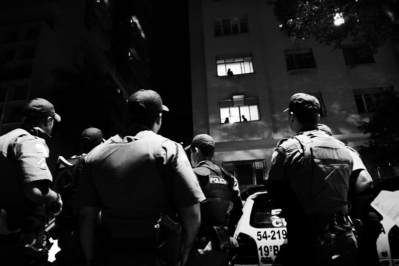 Military police forces surround the area near favela Chapeu Mangueira where the gang shootings erupted, while some residents look on the scene out of windows. June 2007.