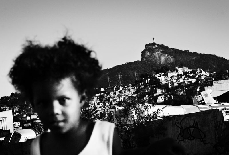 A girl stays at her favela Cidade Nova where poverty, unemployment and violence are rampant, and behind it, the statue of Jesus Christ of Corcovad is seen. May 2007.