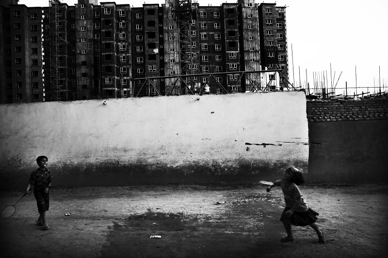 Uighur children play badminton in front of ongoing high-storied modern buildings, as the Chinese modernization projects or Chinesefication expand into Xinjiang. Meanwhile, many parts of Uighur old towns have been destroyed due the Chinese projects.