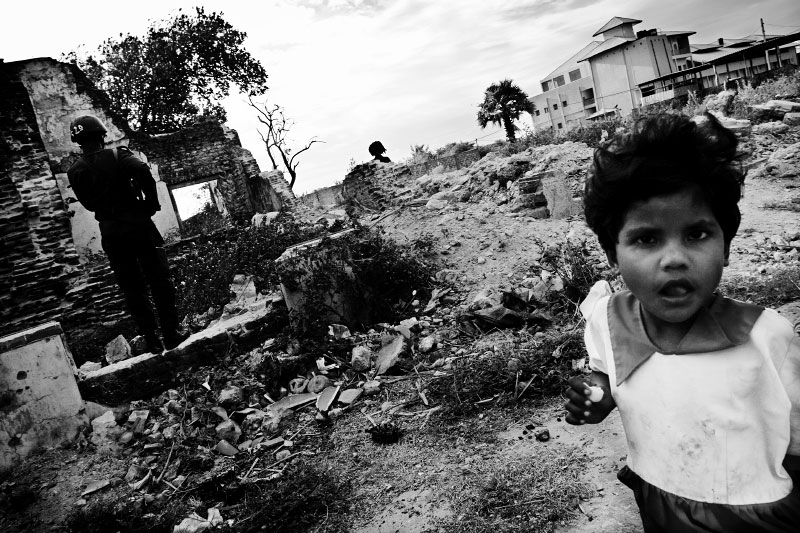 A Tamil girl is hanging out at a war-torn town of Jaffna, while government soldiers patrol. Jaffna is one of the most critical places for LTTE and the Sri Lankan government -- the absolute majority of the town is Tamil but controlled by the government. And in the town, unemployment prevails and many face extreme poverty and dangerous situations due to the long civil war and the current fresh fighting, as well as Tsunami. Jaffna, Sri Lanka, June 23, 2006.