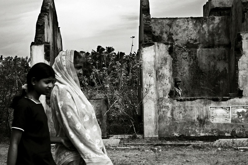 A Tamil mother and a daughter walk through in a war-torn village of Mutur, while a government soldier stay inside of the ruins, as the fresh fighting between the Sri Lankan government and LTTE rebel is dramatically escalating. Mutur, Sri Lanka, June 18, 2006.