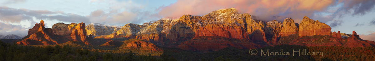 This extra wide panoramic image captures Sedona with a rare afternoon sunset lit cloud, billowing over the red rock formations in central Sedona. A scene such as this is normally present tn the mornings versus afternoons.