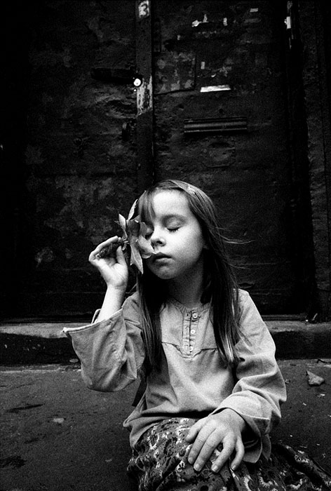 Six year old Mae sitting in front of the older building where her family lives on 5th avenue. Though larger than some buildings on the avenue, it doesn't dominate or alienate. Pete Hamill wrote of the physical changes happening in the neighborhood,