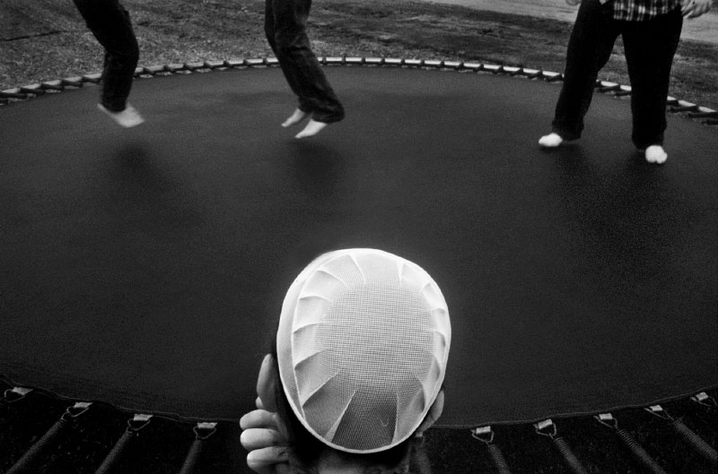 A sister and her brothers play on a trampoline on a Sunday afternoon, Mennonite family, Logan, Ohio