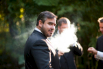The handsome groom looks ever so dashing  with the ethereal cloud of smoke surrounding him.