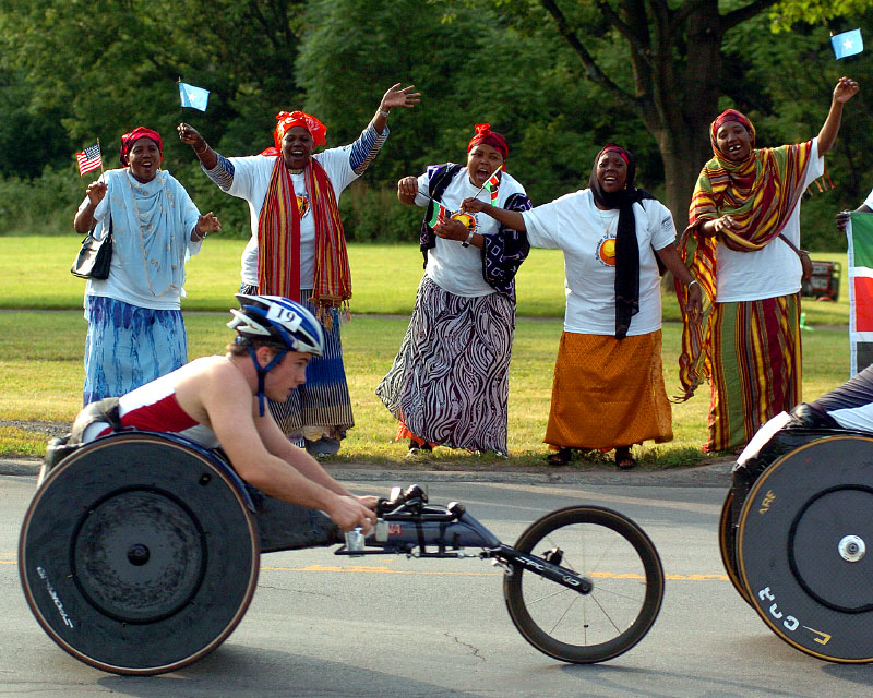Arbay Sebdwto, left, Jamila Dumas, Kerai Mokoma, Madina Musa, and Batula Mokoma, all of Somalia, cheer wheelchair racer Tyler Byers, of Reston, Virginia, on Culver Avenue, near Armory Drive during the 29th Annual Boilermaker 15K Road Race in Utica, Sunday, July 9, 2006. The women were part of the race's new International Mile that displayed the diversity of Utica's newest arrivals.©OBSERVER-DISPATCH/Photo by Marilu Lopez Fretts