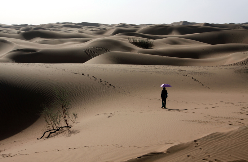 A tourists walks along ointo the Tenngger desert in Ningxia Province.