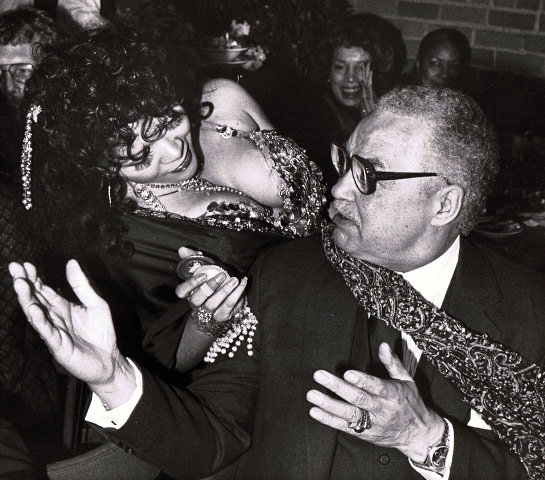 Belly dancer Shareffa Saleh goes through her routine while Detroit Mayor Coleman A. Young gestures during a dinner in the Greektown section of Detroit. The city was in its second day of hosting the Democratic National site inspection committee, March 1983