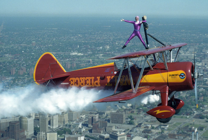 Wing-walker Loria Lynn Ross, 29, of Encino, CA salutes as pilot Walt Pierce, 51, of Sebring, FL, flies his 1940 Stearman biplane over Detrot's Renaissance Center, June 1991.