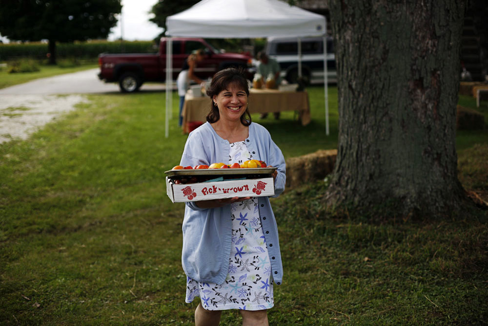 Leslie Cooperband--co-owner of Prairie Fruits Farm carries tomatoes to the kitchen.
