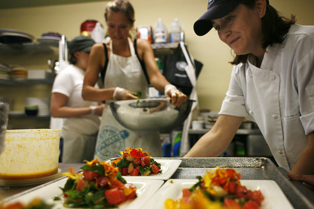 Alisa, the head chef at the farm, helps plate the herb and watermelon salad.