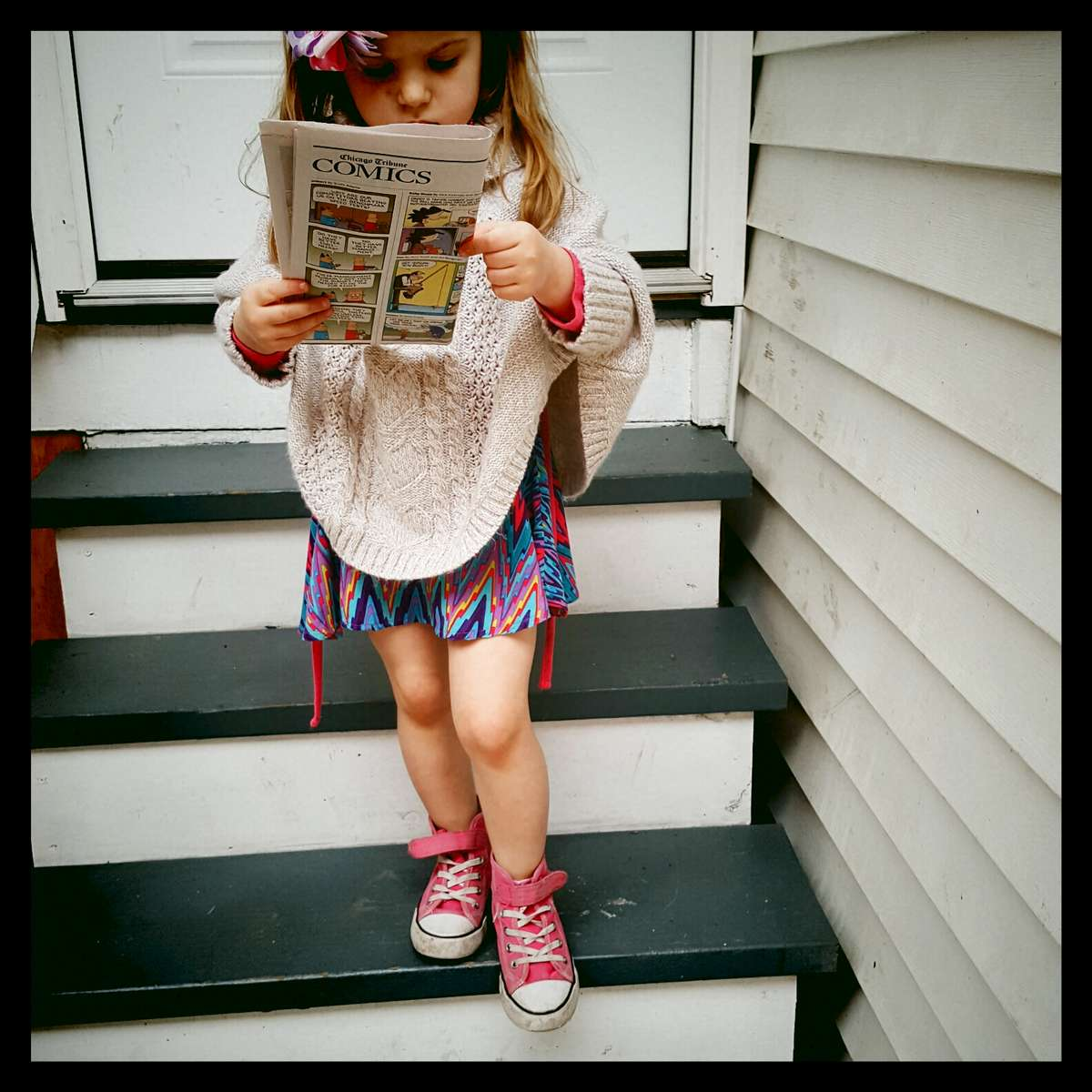 Rose trying to read the comics while slowly descending our stairs. April 2016.