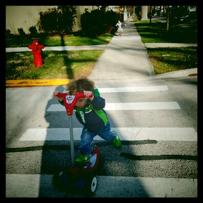 Luka scooting away as fast as he can after he swiped Rose's scooter on they way home. March 2016.