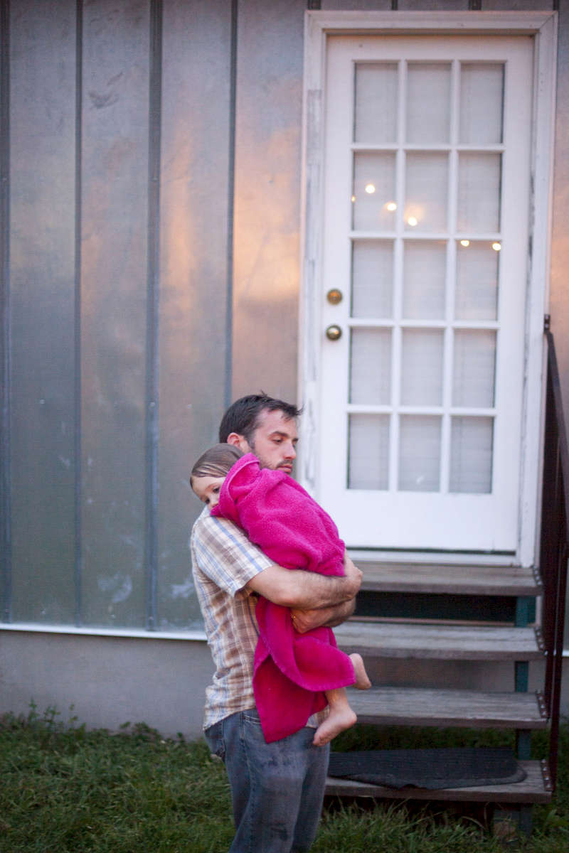 A father holds her daughter (3 yrs old) after a bath on a warm spring day.