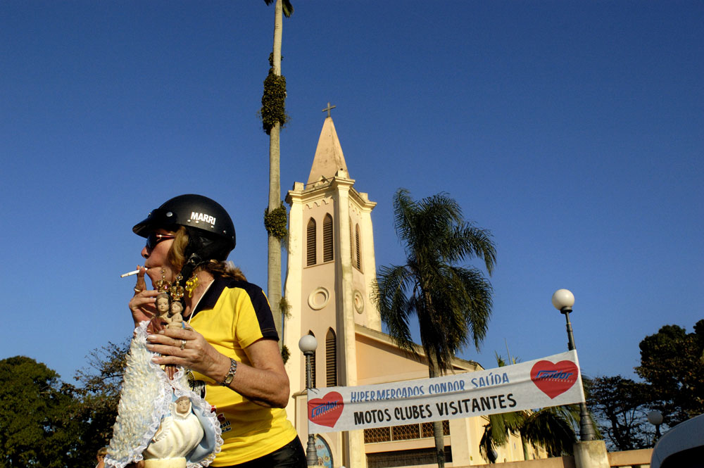 A member of the Moto Clube Robalos Rebeldes holds Our Lady of Rocio before a procession through the city. The procession stated at the  State Shrine of Our Lady of Rocio in Paranaguá, PR, Brazil.