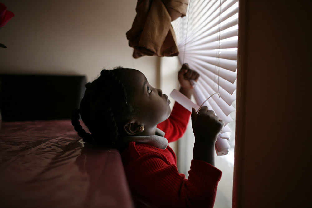 Omnia, Sawson's oldest daughter plays with the blinds in their new suburban home. Sawson and her family left the city because the rent was too high.