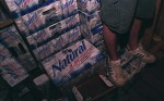 Rocco Tissone stands on a mountain of beer behind the bar at the Theta Chi house during a house party.