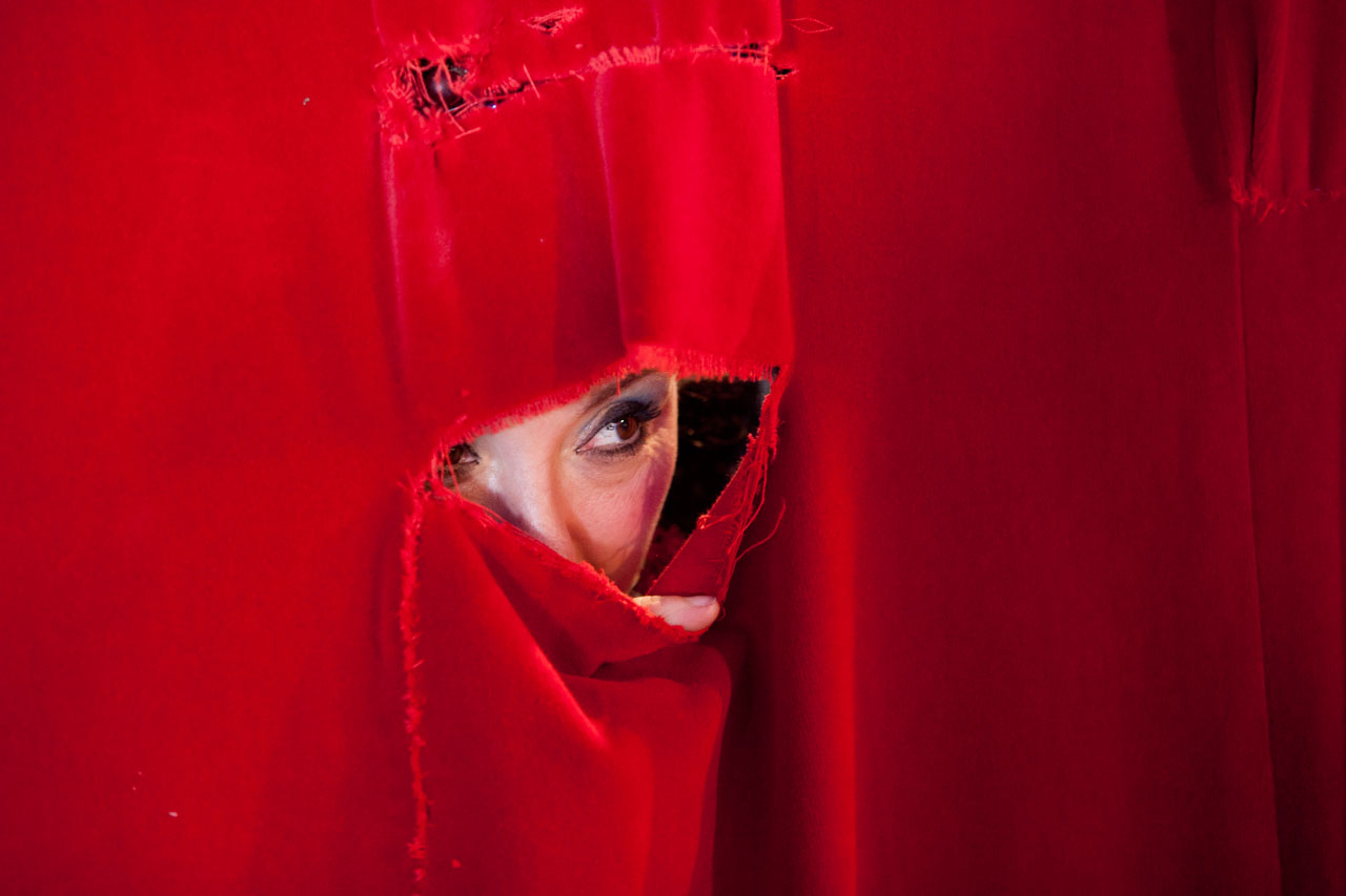 Tosca Zoppe peaks through a hole in the backstage curtain to get a better sense of the crowd that night.