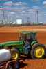 A vertical picture shows a west Texas farmer fueling his green John Deere tractor from a tank on a trailer. The top third of the image is blue sky with white puffy cumulus clouds floating above a petrochemical refinery. The bottom of the picture is red dirt soil that is being tilled by the farmer.