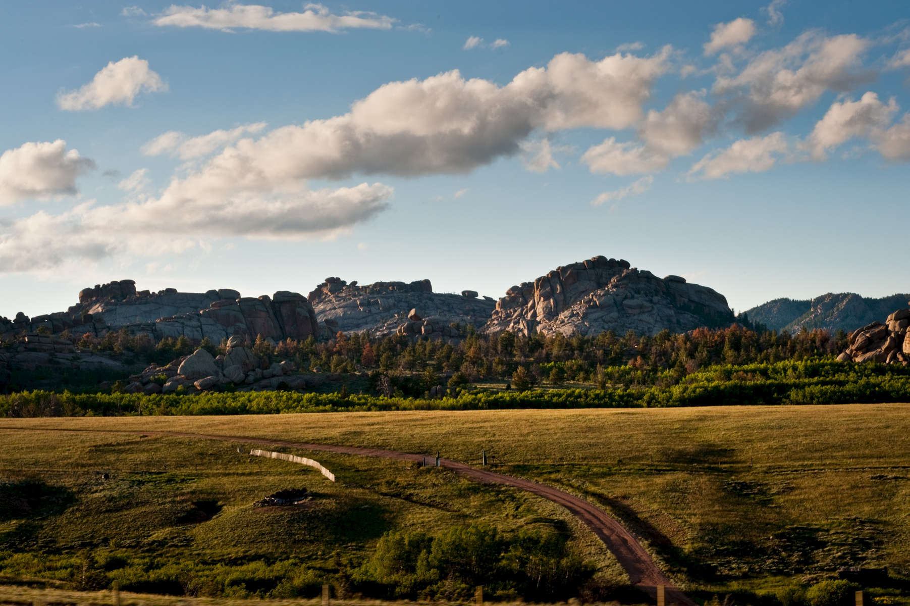 A horizontal panoramic image of a southern Wyoming dirt road that curves gently out of the frame at the bottom of this picture. The two track dirt trail is protected by a snow fence in the grassy area that leads to a forested wooded area with the rocks and boulders of Vedauwoo in the distance underneath a blue sky with clouds.