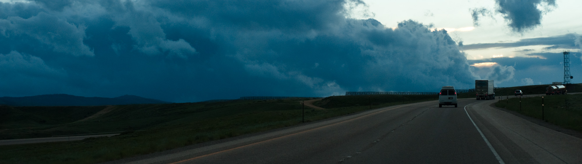 A long, wide panoramic picture of vehicles on the westbound lanes of US Interstate 80 in southern Wyoming with the Rocky Mountains to the far left and cold steel blue storm clouds in the top half of the frame. Snow  fences at the horizon line protect the raodway below from blowing snow. A communications tower sits at the far right of the frame.