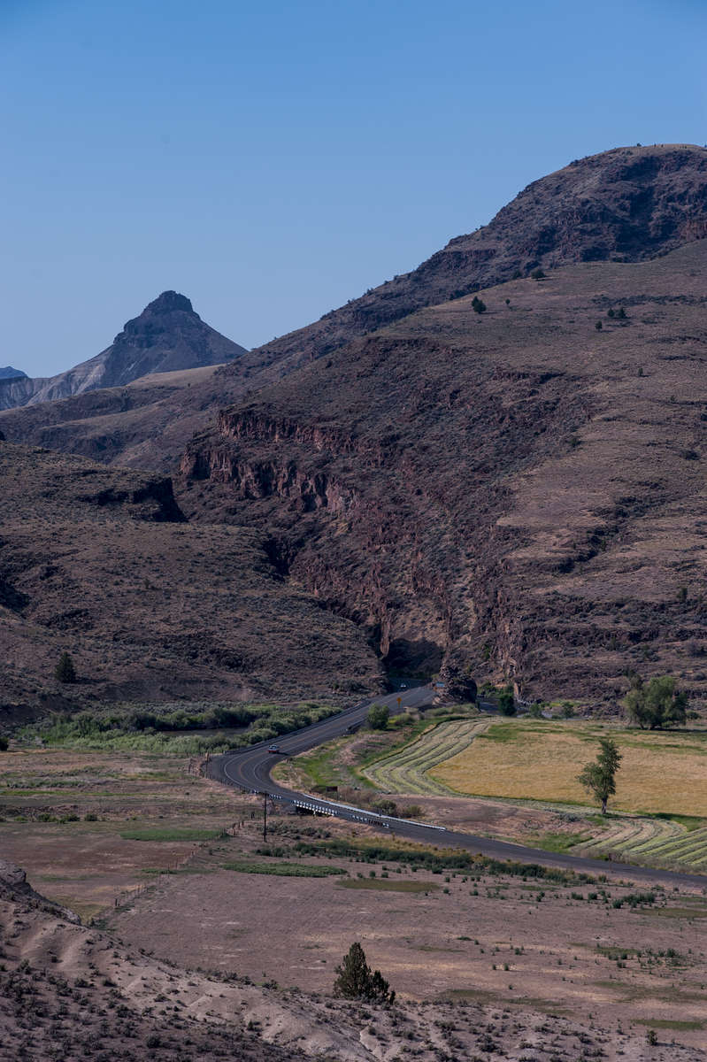 This vertical image feature an S shaped road, US Highway 26, coming out from a deep gorge carved by the John Day River with Sheep Rock Mountain in the background below a clear blue sky. A scenic view of the John Day Fossil Beds National Monument.