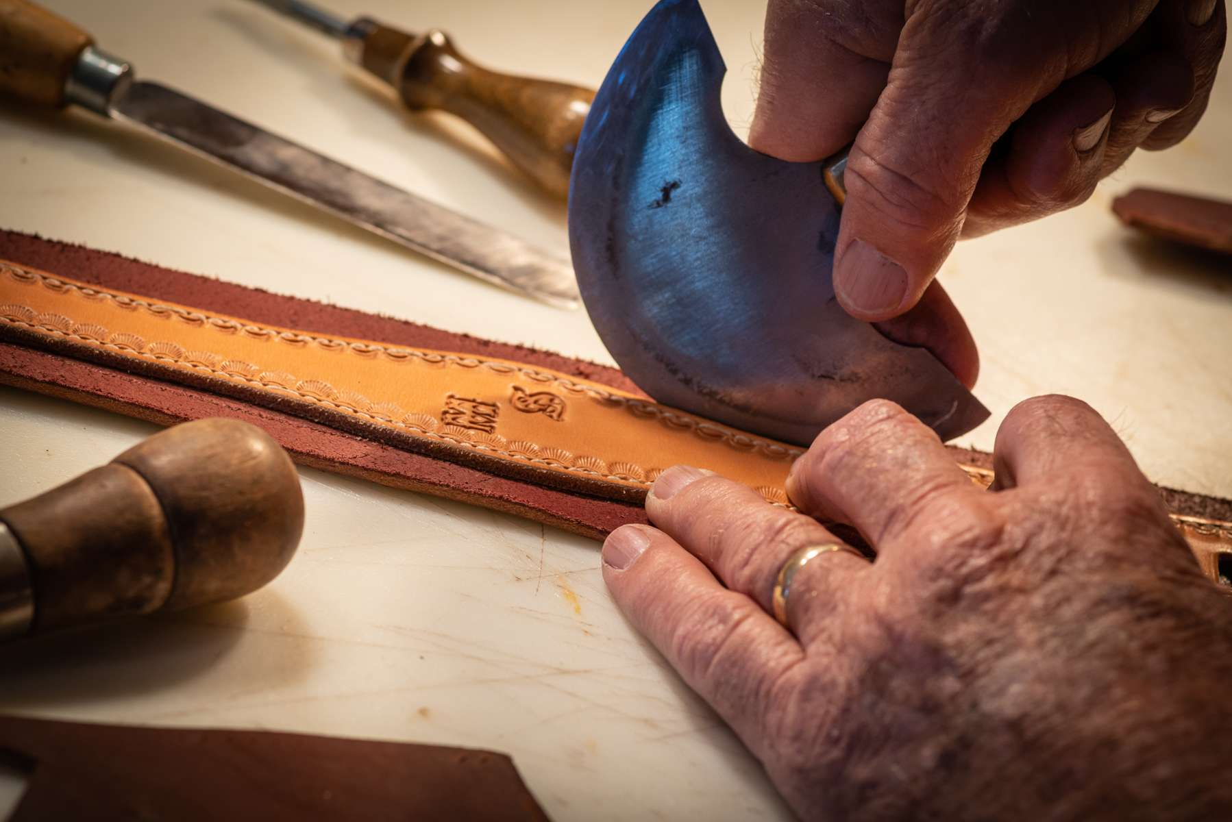 Ray Stokes, an excellent leather craftsman with old, but skilled hands, uses a semi-circular leather cutting knife on a cheek piece for a bridal commissioned by a surgeon from Colorado.