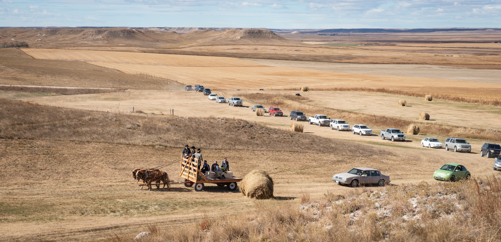 A procession of cars and trucks follows a horse drawn cart with Ray's casket up to the grave site overlooking the Sidney Draw.