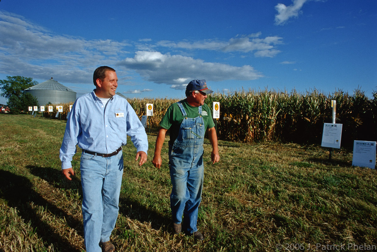 A horizontal picture of a seed dealer and a farmer walking a long a corn test plot. A blue sky with some cumulus clouds at the top of the picture meet with the rows of the corn and seed type signs as they trail off to the left of the frame where a grain bin sits. The men are walking from left to right and are large in the frame near the center.