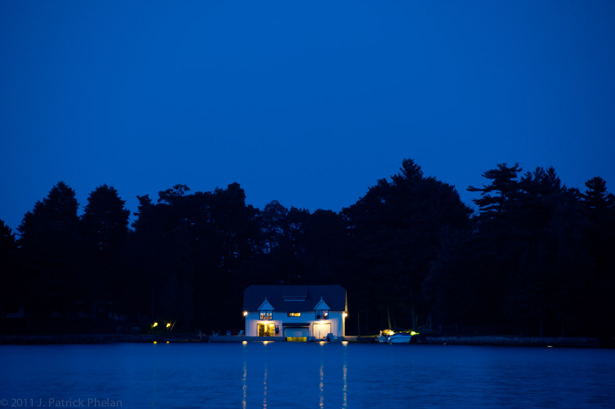 Manhattan Island yacht house lights up the night in the 1000 Islands near Alexandria Bay, NY, on the St. Lawerence Seaway.