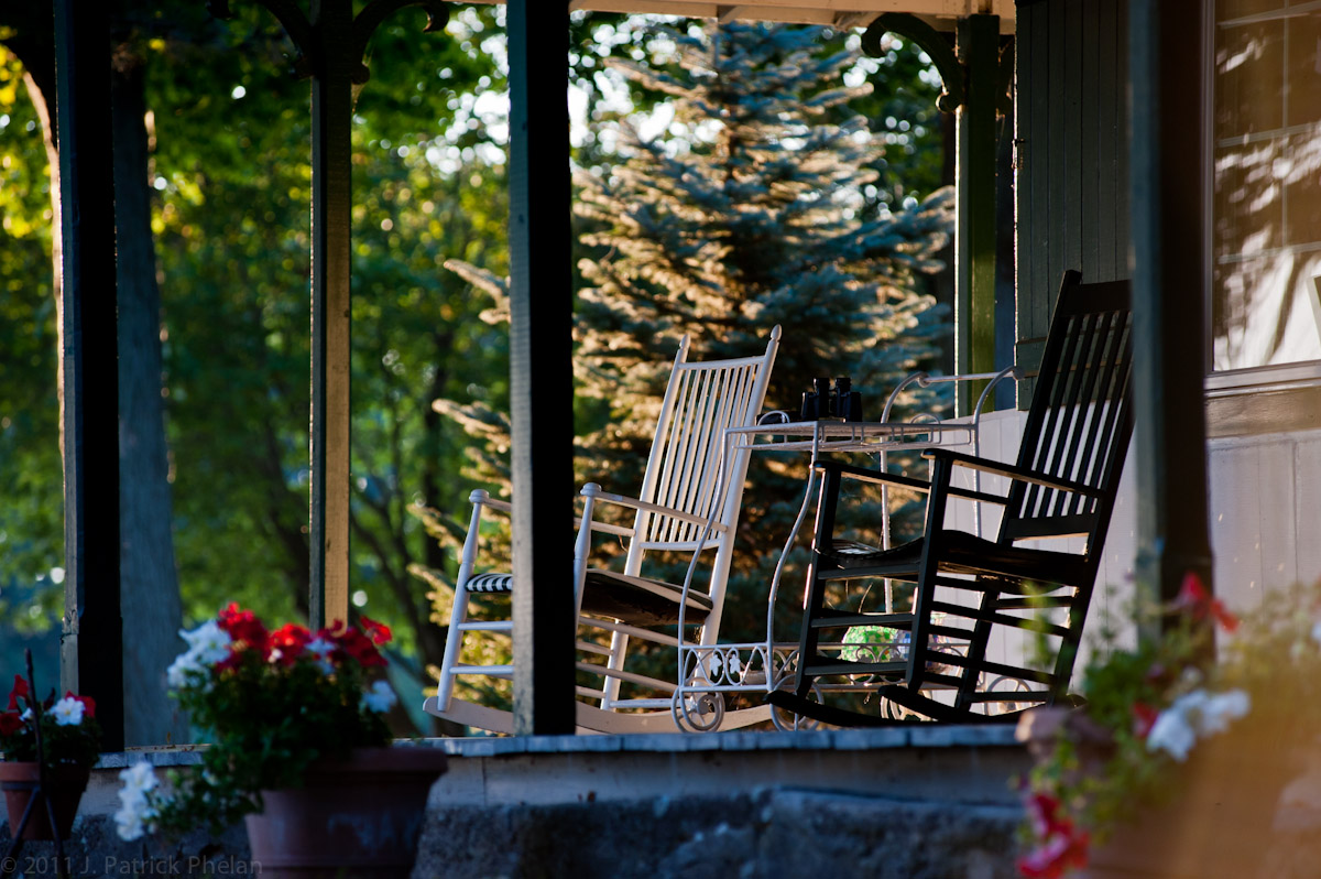 Late afternoon light accents rocking chairs on a porch on Manhattan Island in the 1000 Islands in upstate New York.