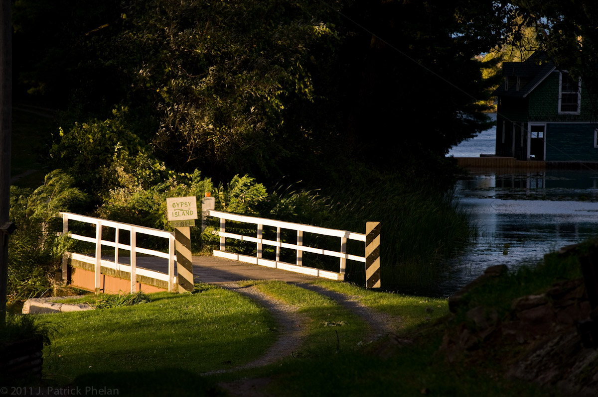 Sunset lights up the Gypsy Island bridge with the boat house shaded in the background