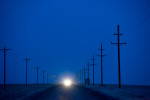 This horizontal picture of receding telephone poles on the left and utility poles on the right align with a gravel country road that tapers off into a flat horizon line in a western Nebraska Panhandle county where night is settling in and the bright headlights of an approaching vehicle are switched on. The night sky and the entire scene have a deep blue color cast. There is a grain bin on the right side of the road near the horizon line.