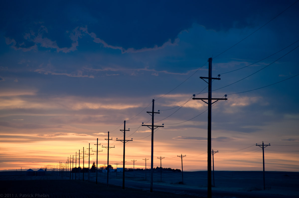 A horizontal picture of power line poles and telephone poles that are parallel to a country dirt road in a rural western Nebraska county as the sunsets to the west with dark clouds at the top of the image and a farmstead surrounded by trees and bushes at the center of the horizon line. Two small grain bins sit on the left side of the frame on the other side of the road from the farm house and out buildings. The sky takes up 4/5ths of the picture.