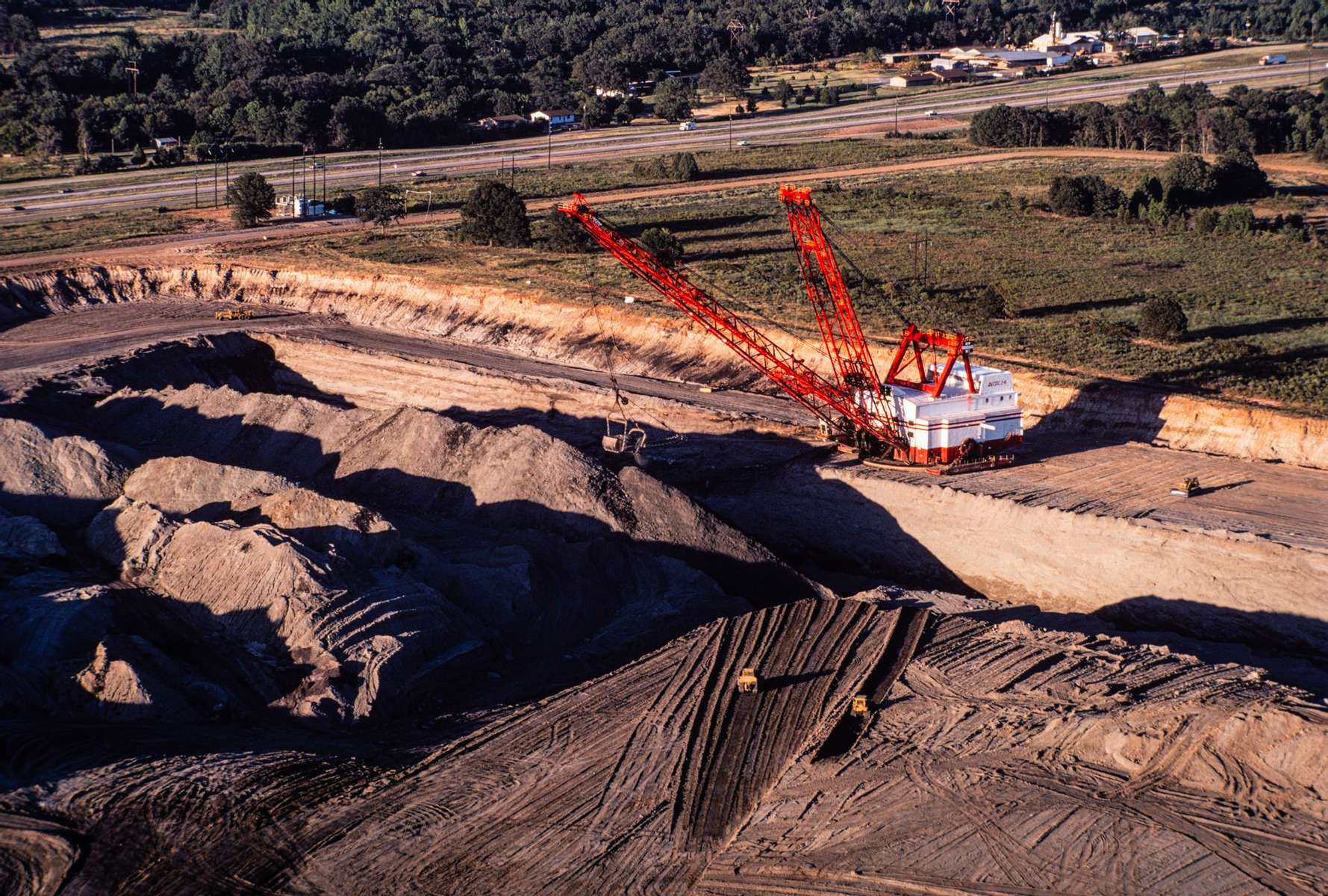 Aerial image of a Bucyrus Erie walking dragline excavating at the Winfield lignite coal strip mine near Interstate 30 and Mt. Pleasant, Texas. Bulldozers, in the foreground, move overbiurden. The mine and the Monticello Power Plant that it fed have now been closed.