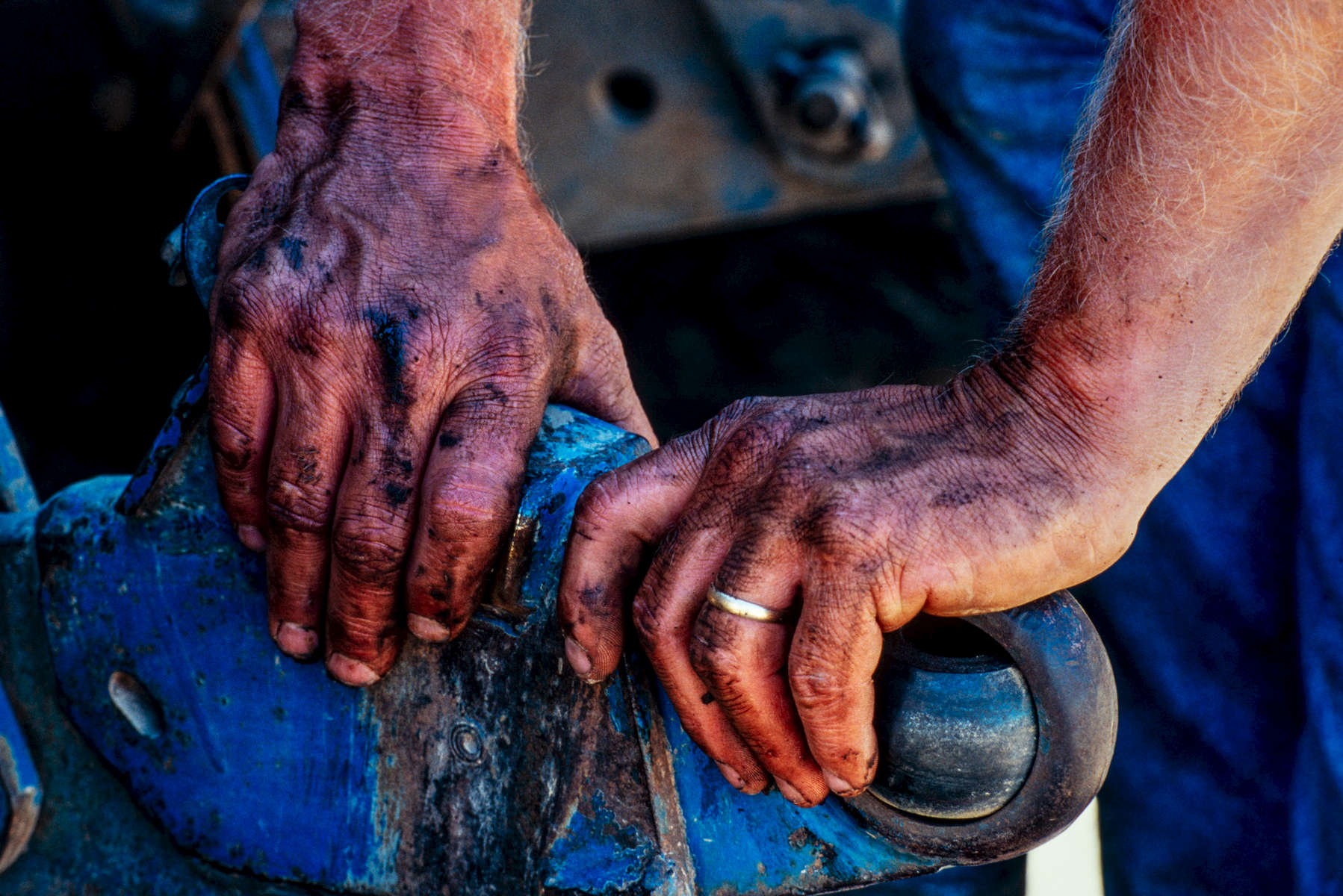 A horizontal picture of a man's dirty and grease covered hands resting on a worn blue tractor part called a 3-point draft link hitch as he takes a break from working on his farm equipment.
