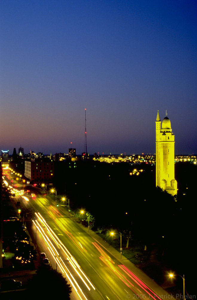 This vertical image was taken at dusk with street lights illuminatinhg South Grand Boulivard, a four lane avenue that connects south and north St. Louis city. The water tower, which is 179 feet tall was constructed in 1898, was built in the French Romanesque style.