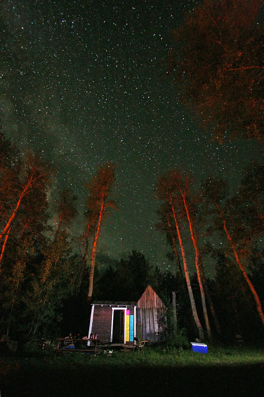 The camp's utility shed is illuminated by campfire late one night at Steens Mountain Running Camp. Many stars can be seen from the camp due to it's high elevation and absence of light pollution in the area.