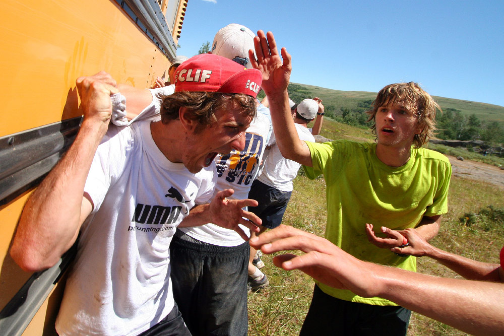 Team members reach for the bus, which represents the finish of the Cross Canyon race.