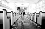 Adria sprinkles rose petals down the center aisle of MacMurray College's Annie Merner Chapel as she prepares for her wedding ceremony. Wedding photography by Steve & Tiffany Warmowski.