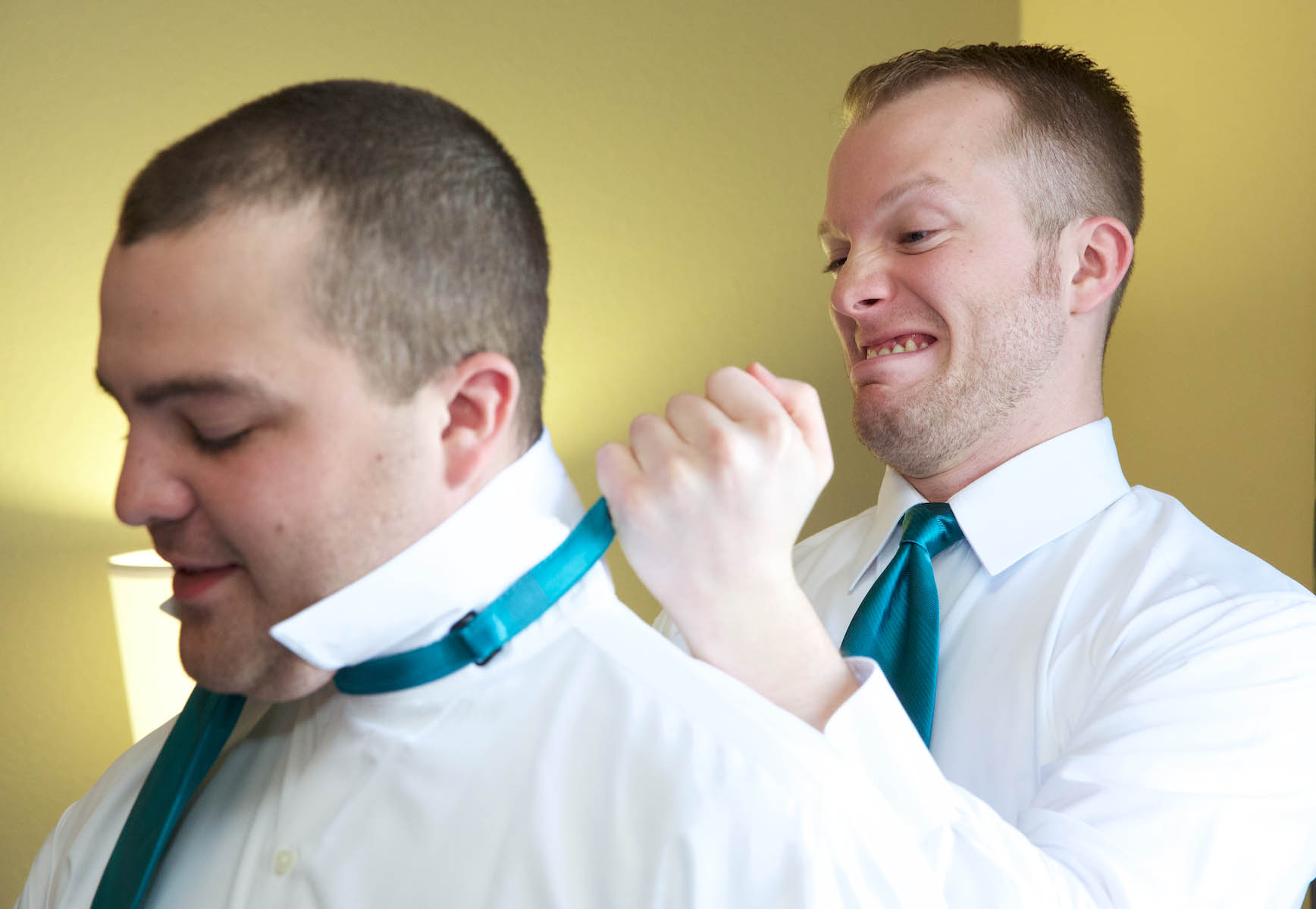 Ben has fun while helping Sam, his brother and best man, as the men get ready at the Hampton Inn, Jacksonville. Wedding pictures by Tiffany & Steve of Warmowski Photography.