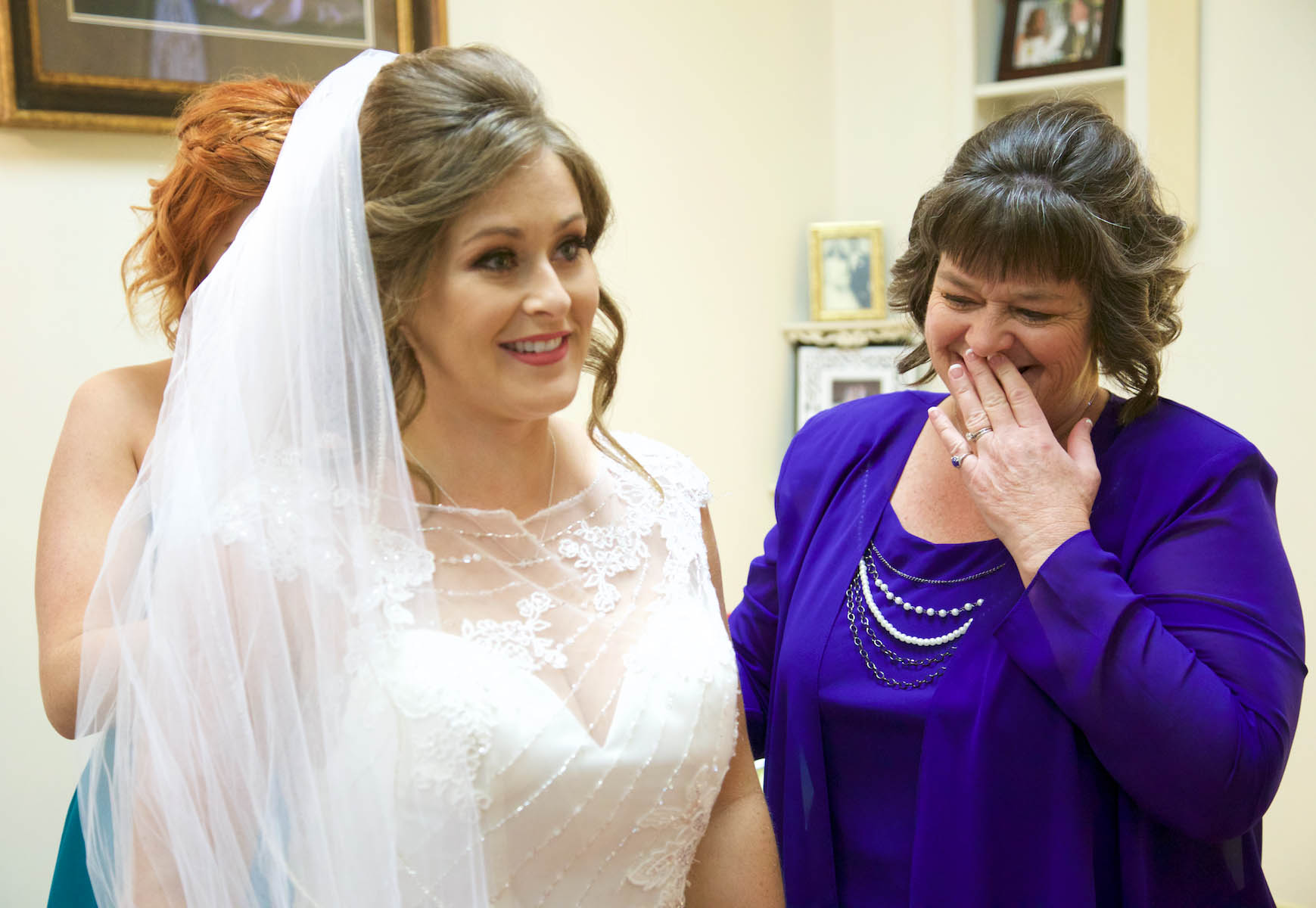 Alissa's mom Sherrie reacts as the bride has her dress buttoned by Laura, the Maid of Honor. Wedding pictures by Tiffany & Steve of Warmowski Photography.