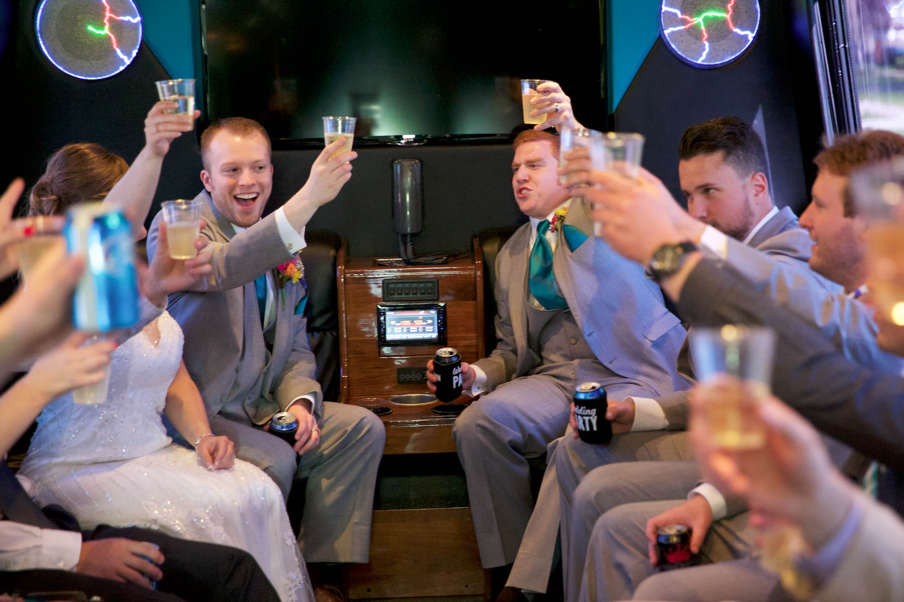 Ben starts the celebration with a toast in the party bus, Executive Transportation. Wedding pictures by Tiffany & Steve of Warmowski Photography.
