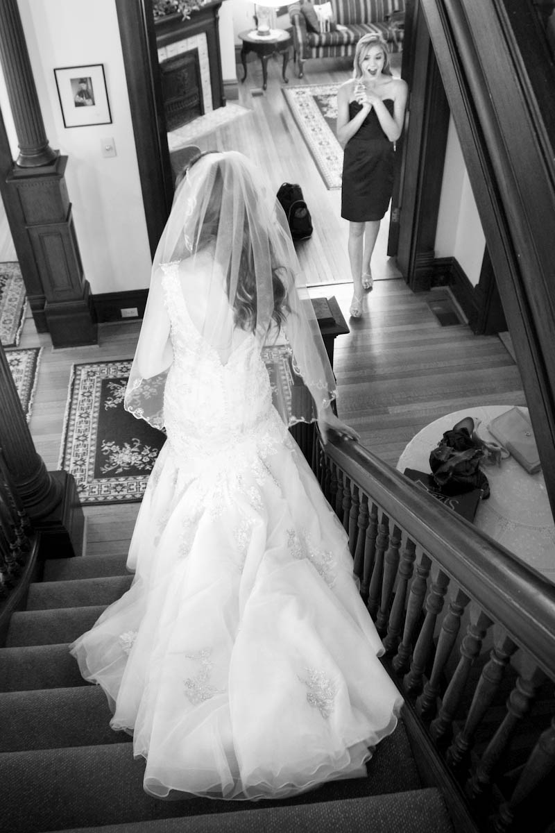 One of the bridesmaids reacts as Alissa comes down after putting on her wedding dress upstairs at the Old Rectory. Wedding ceremony held next door at Our Saviour Catholic Church in Jacksonville. Wedding photography by Tiffany & Steve Warmowski.