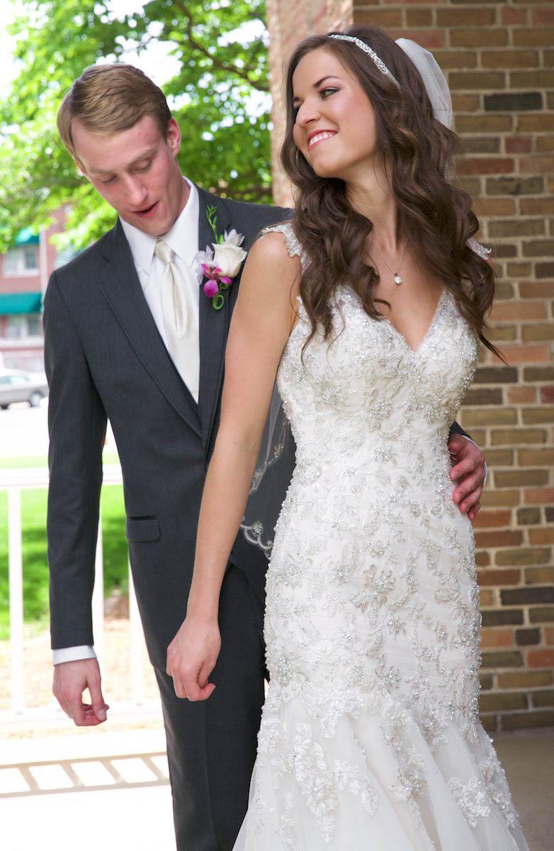 Brandon checks out the detail on Alissa's wedding dress, at Our Saviour Catholic Church, Jacksonville. Wedding photography by Tiffany & Steve Warmowski.
