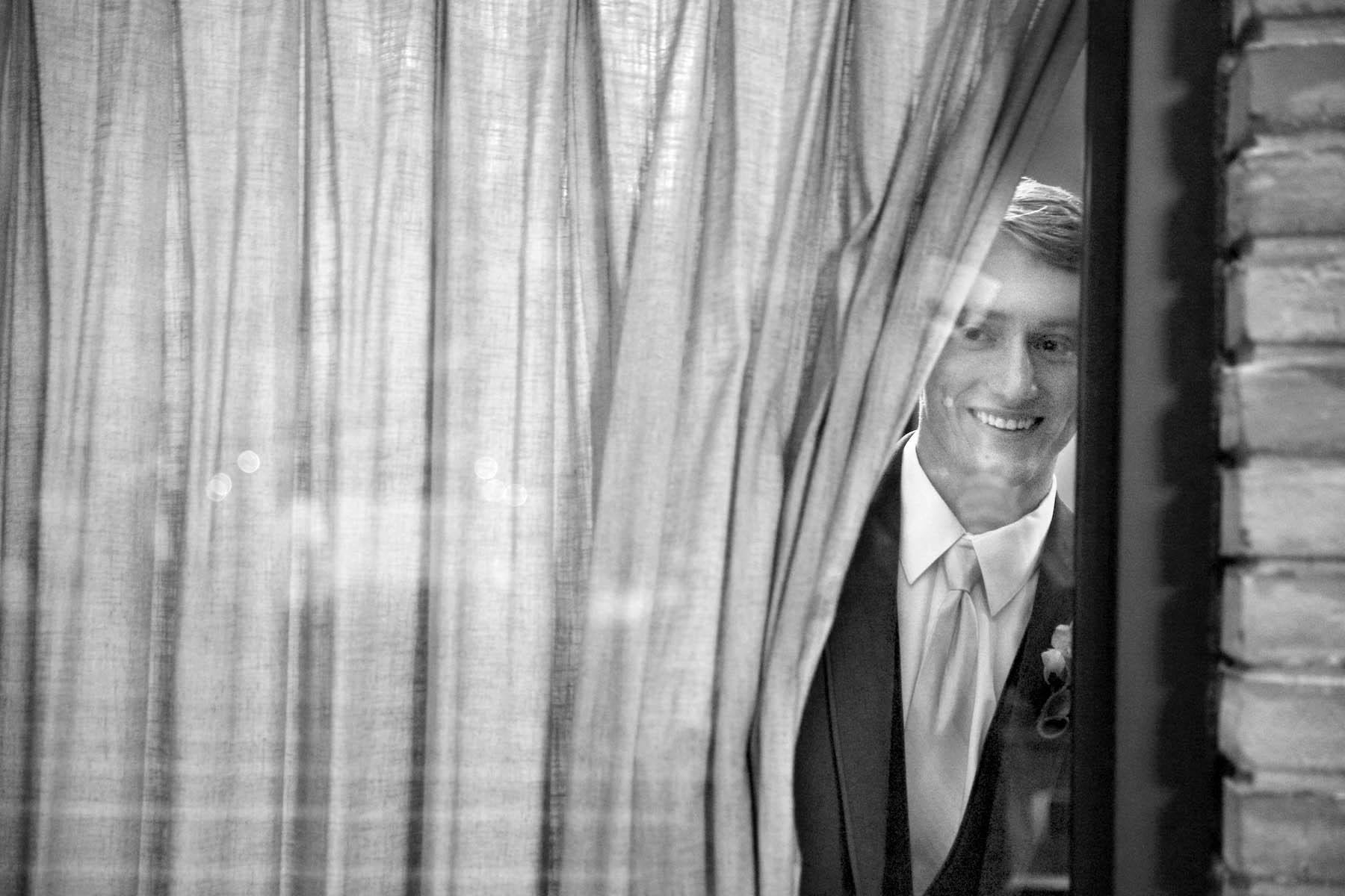 Brandon peeks out as he's sequestered in the room before the ceremony with his groomsmen. Ceremony at Our Saviour Catholic Church, Jacksonville. Wedding photography by Tiffany & Steve Warmowski.
