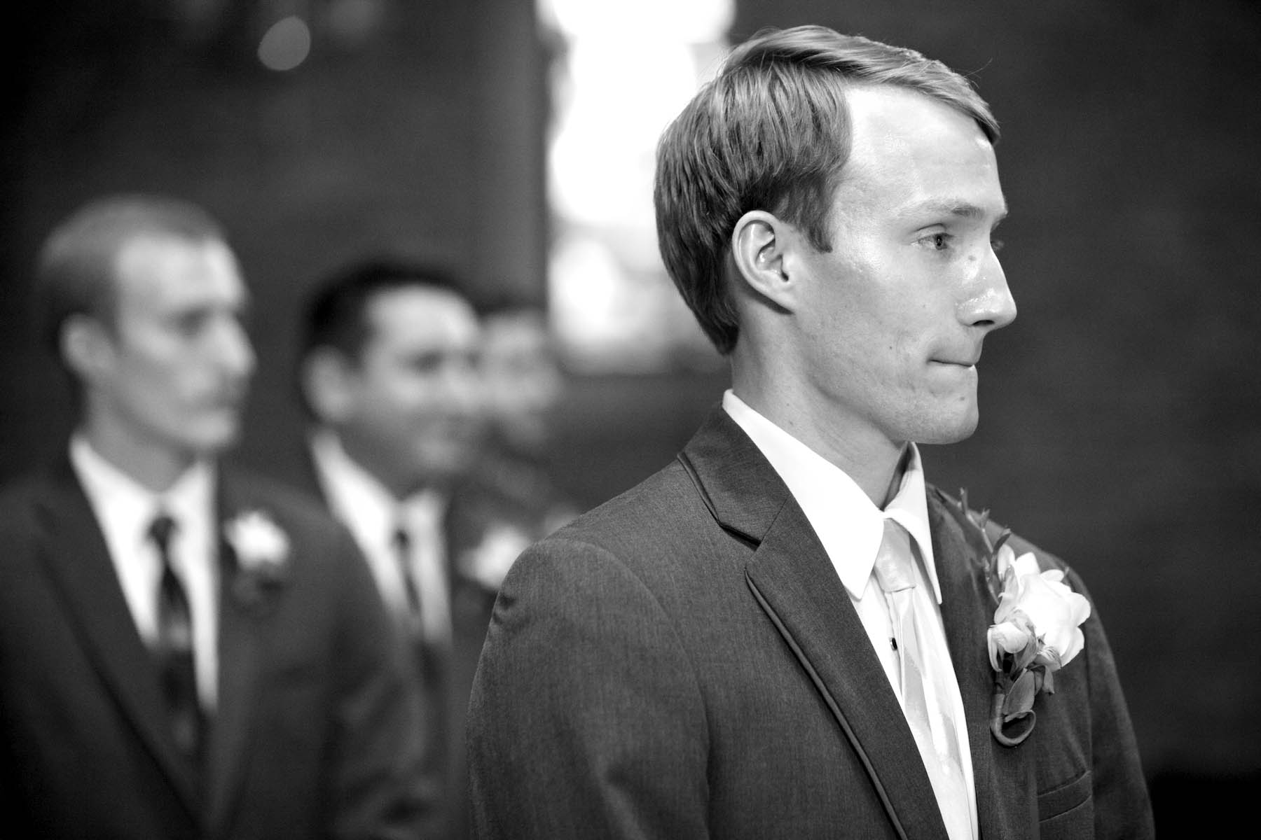 Brandon reacts as Alissa comes down the aisle, ceremony at Our Saviour Catholic Church, Jacksonville. Wedding photography by Tiffany & Steve Warmowski.